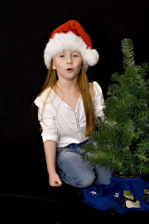 red head girl: A small red head girl in Santa hat decorates her Christmas tree - mouthing the words Ho-Ho-Ho. Stock Photo