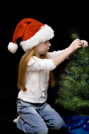 Small girl in jeans and Santa hat decorates her Christmas tree. photo