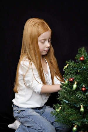minature: A small redhead girl decorates her minature christmas tree.