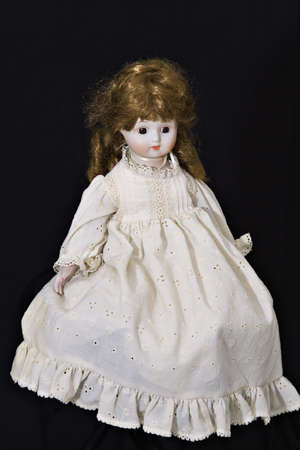 An old doll dressed in old-fashioned dress on black background.