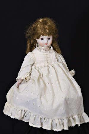Een oude pop gekleed in ouderwetse jurk op zwarte achtergrond.