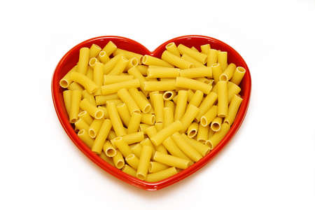 A heart dish filled with rigatoni pasta on white background. Stock Photo