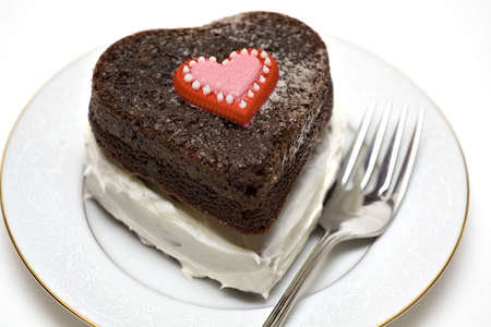A heart shaped chocolate cake on plate with fork. Stock fotó