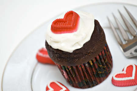 A cupcake on white plate, white icing - candy hearts.