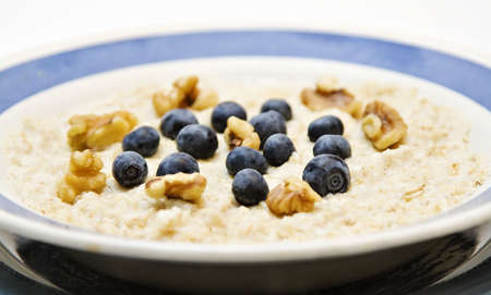 A bowl of oatmeal garnished with blueberries and walnuts - heart healthy breakfast.