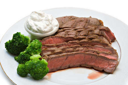 A plate of rare beef with sides of whipped horseradish sauce and broccoli
