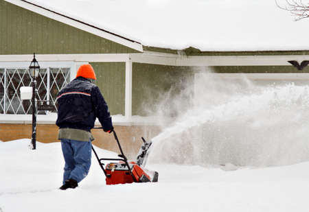 A man uses snowblower to clean his driveway. Stock Photo