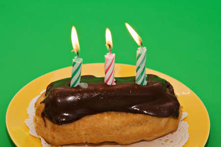 An eclair on yellow plate with three  lit candles. Stock Photo - 2654532