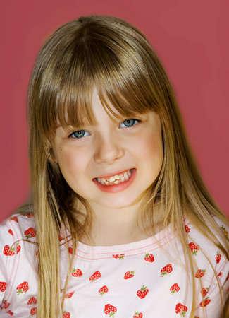Cute blonde girl with very loose  teeth.