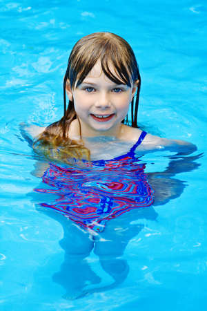 A small girl swimming in pool or water in the summer.