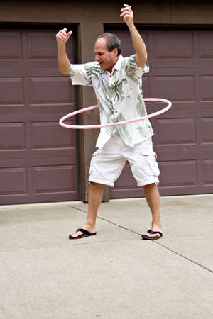 55 years old: A mature man - 55 years old - plays with a hula hoop.