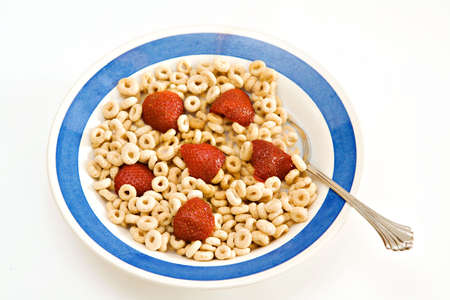 A bowl of oat O cereal with milk and strawberries - breakfast.  On white background Zdjęcie Seryjne