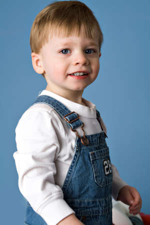 Boy toddler age 2 in bib overalls, blue background.
