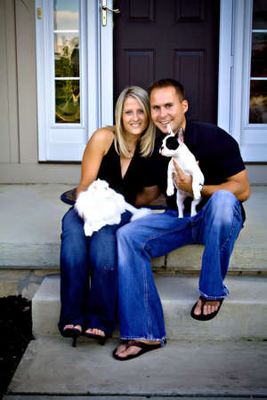 house pet: A husband, wife sit in front of their home with their white cat and French bulldog puppy.