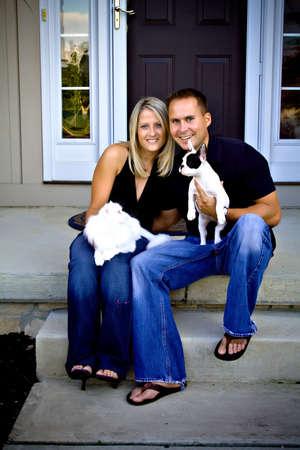 mujer con perro: El marido, la esposa se sientan en frente de su hogar con su gato blanco y cachorro bulldog franc�s. Foto de archivo