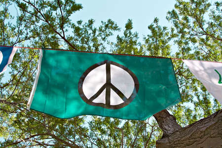 peace flag: A peace flag flies in trees during a peace rally in Cleveland Ohio on Labor Day 2008. Stock Photo