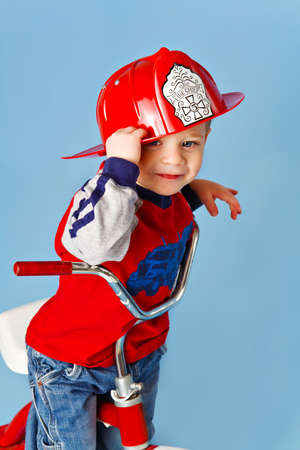A two year old toddler wearing a firemans helmet plays fireman on his tricycle.
