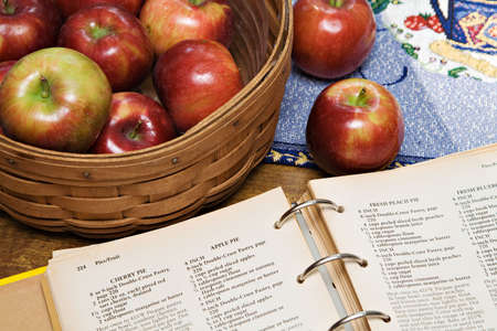 A recipe book turned to apple pie recipe - basket of apples.  版權商用圖片
