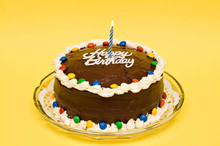 A chocolate birthday cake with candy, candle and icing.