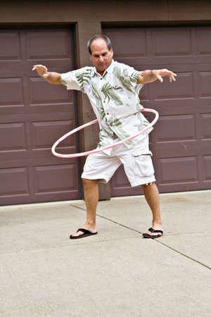 old year: Cinquanta-cinque anni, l'uomo gioca con un hula hoop.