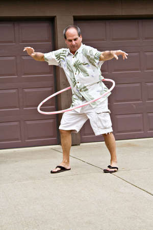 five year old: Fifty-five year old man plays with a hula hoop.