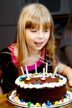Eight year-old girl blows out her birthday candles on her cake photo