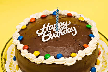 Chocolate Birthday cake with candle on yellow background.  Stock Photo