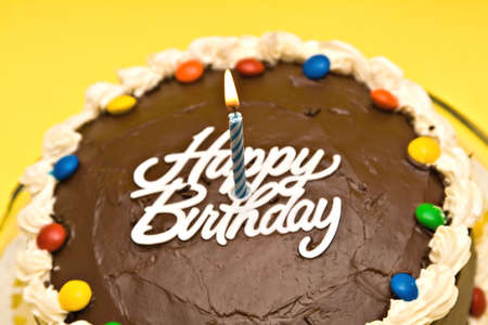 Chocolate Birthday cake with candle on yellow background. Shallow depth of field - focus on candle.  photo