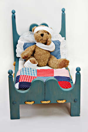 A small bear in a toy bed wrapped in bandages.