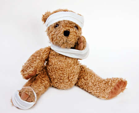 Bear with bandages on head, arm, foot. Stock Photo