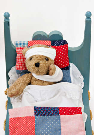 A teddy bear wrapped in bandages recovering in bed.  photo