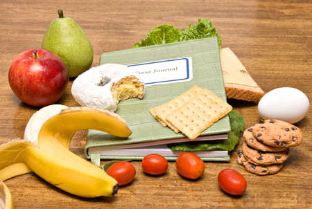 Food Diary - Journal in the middle of foods.  A health diet concept.