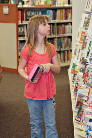 reading material: A elementary school-age child browsing library shelves for materials to borrow.
