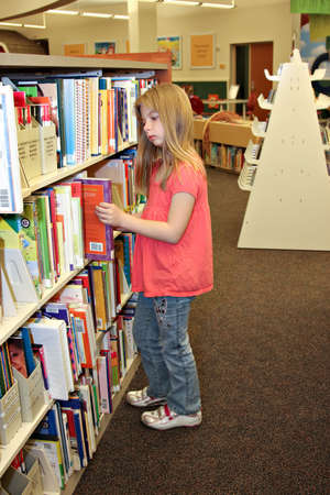 A school agied girl looks at books on bookshelf in library.