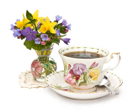 A vase of spring flowers and a teacup on white background photo