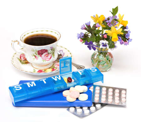 A still life scene with teacup, vase of spring flowers, assorted pills, drugs, vitamins, and dispensers.  Stock Photo