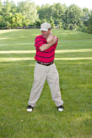 limber: Man doing several stretching exercises before round of golf.
