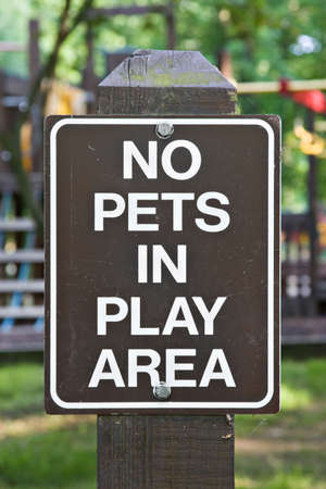 A sign indicated no pets allowed in childrens play area.  photo