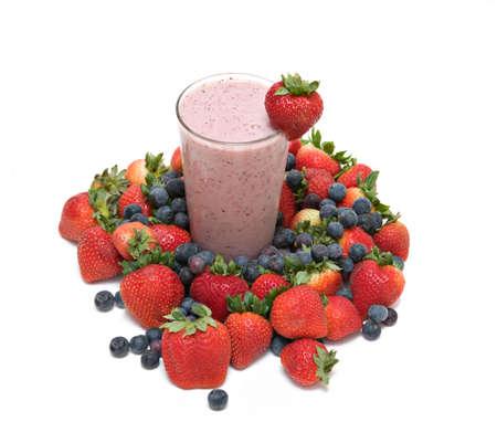 tall glass: Strawberry Blueberry, banana,  Fruit  Smoothie in tall glass - strawberry garnish surrounded by fresh fruit against white.