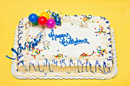 Large decorated Birthday cake with white icing, sprinkles, ribbons, balloons. photo