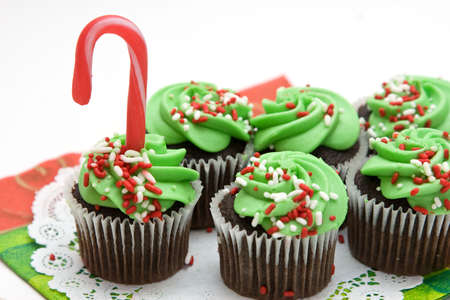 Christmas cupcakes topped with frosting, sprinkles and candy cane.  photo