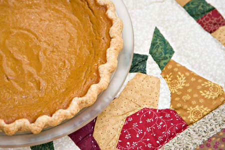 A fresh homemade pumpkin pie on a quilted table cloth. photo