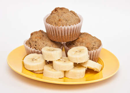 banana: Yellow plate of sliced fresh banana and home-baked muffins.