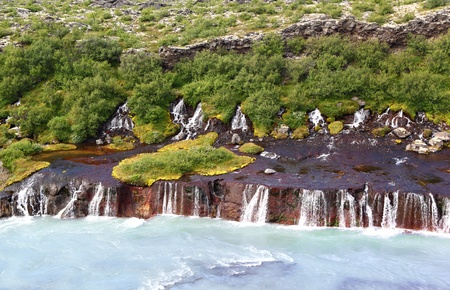 The blue mineral waters of Hraunfossar falls in Iceland Stock Photo