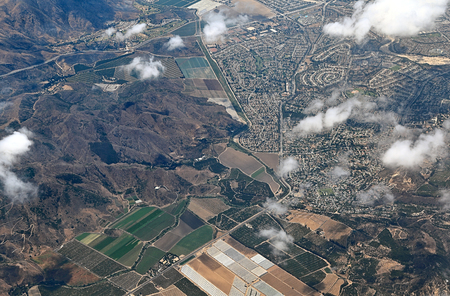 Aerial view of California landscape with agriculture, suburbs, and mountains