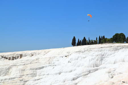 Pamukkale: Paraglider flying over the caclium deposits from the natural thermal springs. Stock Photo