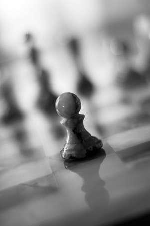 strategic advantage: Lone Pawn on a chess board - slighty grainy bw image, shallow dof