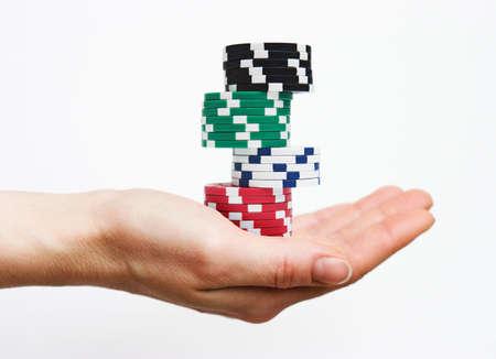 Isolated hand holding casino/poker chips - gambling concept perhaps??? Standard-Bild
