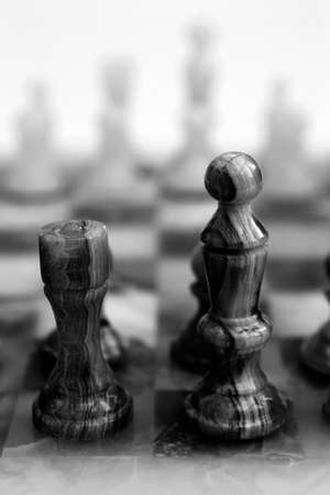 king and queen: Onyx King & Queen pieces on a chess board - quite grainy bw image Stock Photo