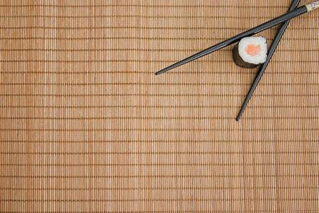Sushi & chopsticks on a bamboo mat Standard-Bild